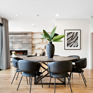 Photo of a contemporary open plan dining in Sydney with white walls, medium hardwood floors and brown floor.