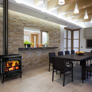 Example of a mid-sized minimalist vinyl floor and beige floor kitchen/dining room combo design in Seattle with white walls, a hanging fireplace and a metal fireplace