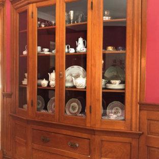 Ispirazione per un'ampia sala da pranzo vittoriana chiusa con pareti rosse, pavimento in legno massello medio, camino classico, cornice del camino in legno e pavimento marrone