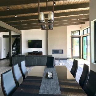 Esempio di una grande sala da pranzo aperta verso il soggiorno minimalista con pareti bianche, pavimento in laminato, camino lineare Ribbon, cornice del camino in intonaco e pavimento beige
