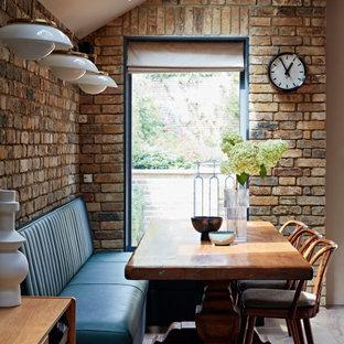 Cette photo montre une salle à manger ouverte sur la cuisine chic avec un sol en bois clair, un mur en parement de brique, un mur blanc et aucune cheminée.