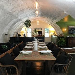Esempio di una grande sala da pranzo aperta verso la cucina mediterranea con pareti bianche, pavimento in legno verniciato e pavimento nero
