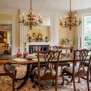Foto di una grande sala da pranzo classica chiusa con pareti gialle, pavimento in legno massello medio e camino classico