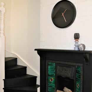 Foto di una piccola sala da pranzo aperta verso il soggiorno vittoriana con pareti grigie, parquet chiaro, camino classico e cornice del camino in legno