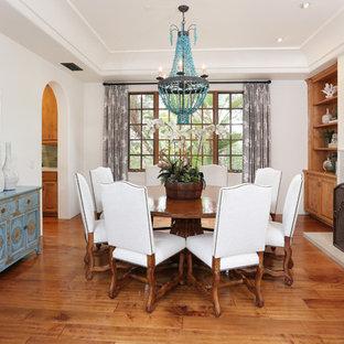Esempio di una sala da pranzo mediterranea con pareti bianche, pavimento in legno massello medio, camino classico e cornice del camino piastrellata