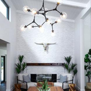 Cette image montre une salle à manger design fermée et de taille moyenne avec un mur blanc, un sol en bois brun, une cheminée double-face, un manteau de cheminée en pierre de parement, un sol marron et un plafond voûté.