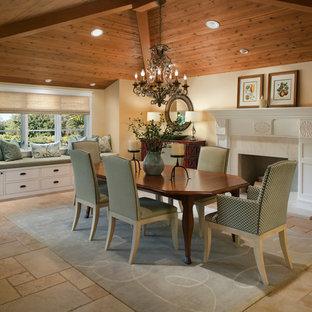 Immagine di una sala da pranzo tradizionale chiusa e di medie dimensioni con pareti beige, pavimento in travertino e camino classico