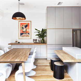 Photo of a mid-sized contemporary dining room in Sydney with light hardwood floors, white walls and no fireplace.