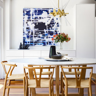 This is an example of a small contemporary dining room in Sydney with white walls, brown floor and medium hardwood floors.