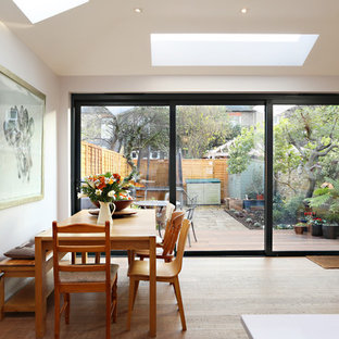 Contemporary open plan dining room in London with white walls, medium hardwood flooring and brown floors.