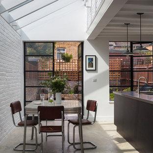 Foto de comedor de cocina contemporáneo con paredes blancas y suelo de cemento