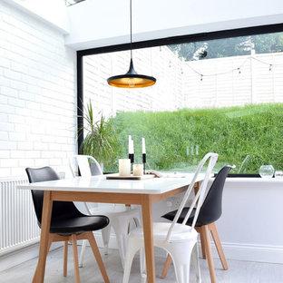 Idée de décoration pour une salle à manger nordique avec un mur blanc, un sol gris, un plafond voûté et un mur en parement de brique.