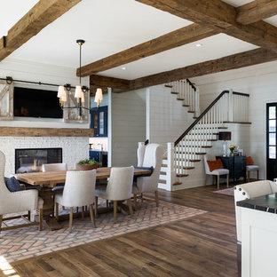 Idee per una grande sala da pranzo aperta verso la cucina costiera con pareti bianche, pavimento in legno massello medio, camino bifacciale, cornice del camino in mattoni e pavimento marrone
