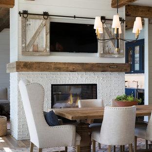 Idéer för stora maritima kök med matplatser, med vita väggar, mellanmörkt trägolv, en dubbelsidig öppen spis, en spiselkrans i tegelsten och brunt golv