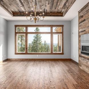 他の地域のラスティックスタイルのおしゃれな独立型ダイニング (グレーの壁、無垢フローリング、吊り下げ式暖炉、木材の暖炉まわり、茶色い床、板張り天井、板張り壁) の写真