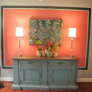 Imagen de comedor bohemio, de tamaño medio, cerrado, con parades naranjas y suelo de madera oscura