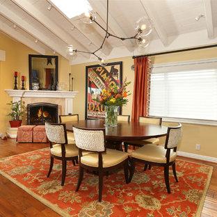 Diseño de comedor ecléctico, de tamaño medio, abierto, con suelo de madera en tonos medios, suelo marrón, chimenea de esquina, paredes blancas y marco de chimenea de piedra