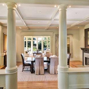 Foto de comedor tradicional, de tamaño medio, con paredes beige, suelo de madera clara, chimenea tradicional, marco de chimenea de madera y suelo marrón