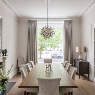 Photo of a classic enclosed dining room in London with beige walls, medium hardwood flooring, a standard fireplace and brown floors.
