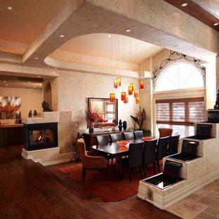 Diseño de comedor ecléctico, de tamaño medio, cerrado, con paredes beige, suelo de madera oscura, chimenea de doble cara y marco de chimenea de metal