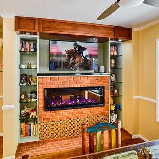 Diseño de comedor de cocina bohemio, de tamaño medio, con suelo de cemento, suelo marrón, paredes amarillas, chimenea de doble cara y marco de chimenea de ladrillo
