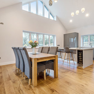 Design ideas for a medium sized contemporary open plan dining room in Dorset with white walls, medium hardwood flooring, no fireplace and brown floors.