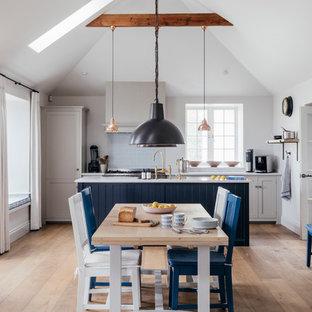 На фото: с высоким бюджетом гостиные-столовые среднего размера в морском стиле с паркетным полом среднего тона, коричневым полом и белыми стенами