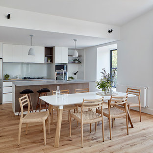 This is an example of a contemporary kitchen/dining combo in Melbourne with white walls, light hardwood floors and brown floor.