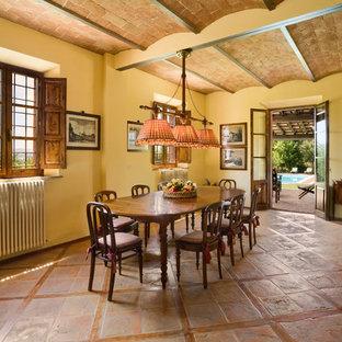 На фото: столовая в стиле кантри с желтыми стенами, полом из терракотовой плитки и коричневым полом