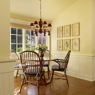 Rural dining room in Seattle with yellow walls and dark hardwood flooring.