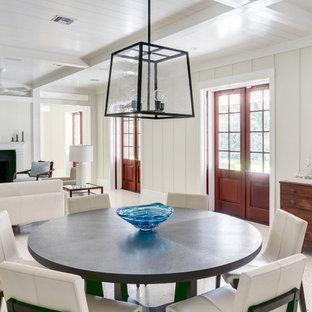 Immagine di una sala da pranzo aperta verso il soggiorno stile marino di medie dimensioni con pareti bianche, pavimento in cemento, camino classico, cornice del camino in cemento e pavimento bianco