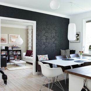 Immagine di una sala da pranzo aperta verso la cucina minimal di medie dimensioni con pareti nere e parquet chiaro