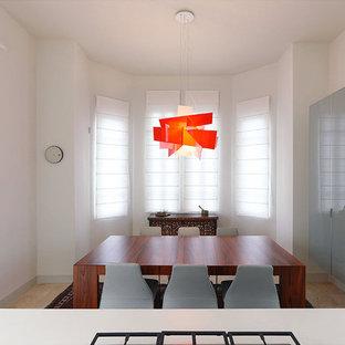 Foto di una sala da pranzo aperta verso la cucina minimalista di medie dimensioni con pareti bianche, pavimento in pietra calcarea e nessun camino