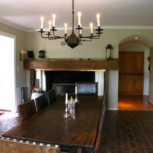 Ejemplo de comedor de cocina clásico, grande, con paredes blancas, suelo de ladrillo, chimenea tradicional y marco de chimenea de madera