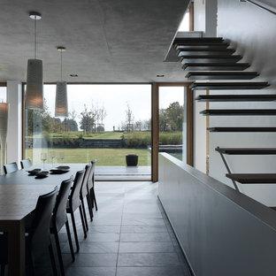 Стильный дизайн: столовая в стиле модернизм с белыми стенами и полом из сланца - последний тренд
