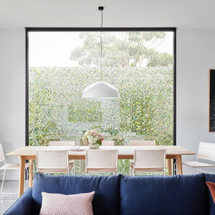 Design ideas for a modern dining room in Melbourne with white walls, concrete floors and grey floor.
