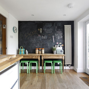 Design ideas for a medium sized scandinavian kitchen/dining room in Sussex with white walls, medium hardwood flooring, no fireplace and brown floors.