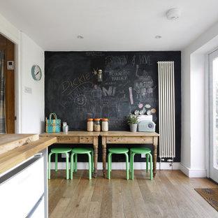 Idee per una sala da pranzo aperta verso la cucina scandinava di medie dimensioni con pareti bianche, pavimento in legno massello medio, nessun camino e pavimento marrone