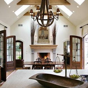Пример оригинального дизайна интерьера: гостиная-столовая среднего размера в стиле кантри с белыми стенами, светлым паркетным полом, камином, фасадом камина из штукатурки и коричневым полом