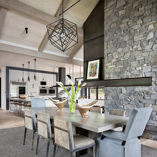 Farmhouse light wood floor and beige floor kitchen/dining room combo photo in Other with a two-sided fireplace