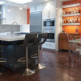 Ispirazione per una piccola sala da pranzo aperta verso la cucina eclettica con pareti arancioni e parquet scuro