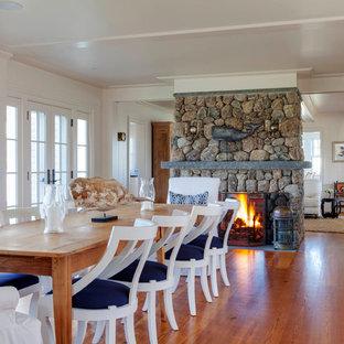 プロビデンスの大きいビーチスタイルのおしゃれなLDK (白い壁、両方向型暖炉、石材の暖炉まわり、淡色無垢フローリング) の写真