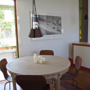 Esempio di una piccola sala da pranzo aperta verso il soggiorno contemporanea con pareti bianche, parquet chiaro, camino classico, cornice del camino in metallo e pavimento arancione