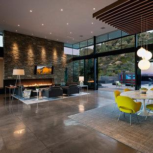 Diseño de comedor moderno, grande, abierto, con paredes multicolor, suelo de cemento, chimenea lineal, marco de chimenea de piedra y suelo gris