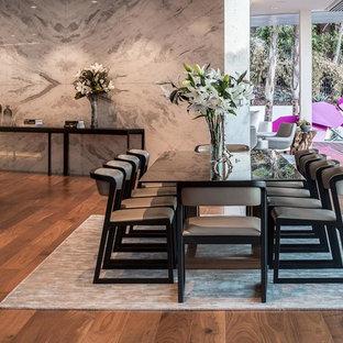 Bild på en mycket stor funkis matplats med öppen planlösning, med grå väggar, mellanmörkt trägolv, en bred öppen spis och en spiselkrans i sten