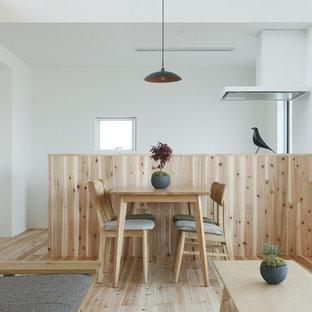 Aménagement d'une petite salle à manger ouverte sur le salon asiatique avec un mur blanc, un sol en bois clair et un sol beige.