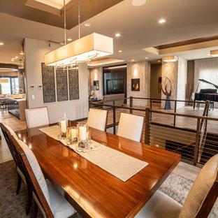 Exemple d'une salle à manger ouverte sur le salon avec un mur beige, un sol en carrelage de porcelaine, cheminée suspendue, un manteau de cheminée en pierre de parement, un sol beige et un plafond en bois.