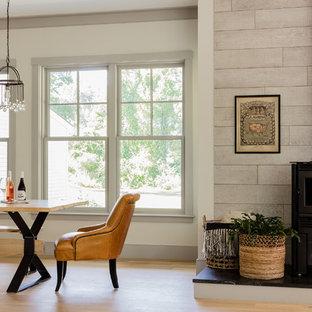 Idee per un'ampia sala da pranzo aperta verso il soggiorno country con pareti bianche, parquet chiaro, stufa a legna e pavimento marrone