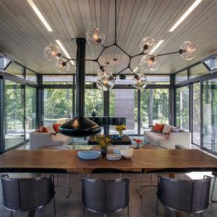 Inspiration pour une salle à manger ouverte sur le salon design avec béton au sol et cheminée suspendue.