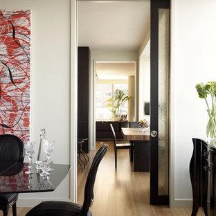 Idée de décoration pour une salle à manger design avec un mur blanc et un sol en bois clair.